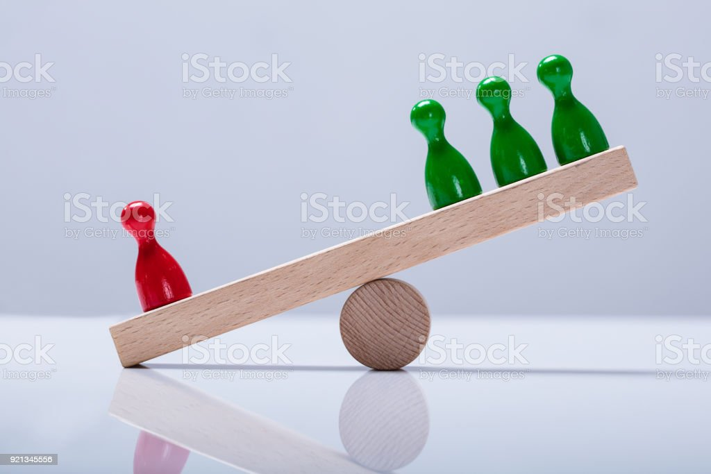 Pawns Figures On Wooden Seesaw stock photo