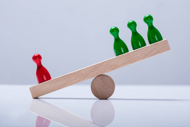 pawns figures on wooden seesaw - scale stock photos and pictures