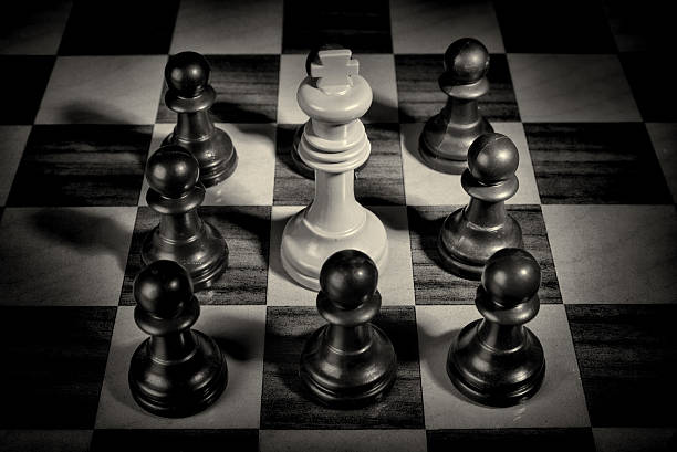 Pawns surrounding king stock photo
