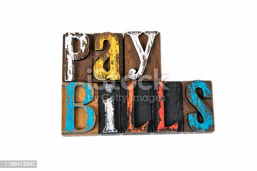 Pay Bills. Finance, taxes, debt and liabilities, abstract background. Colored wooden letters on a white background