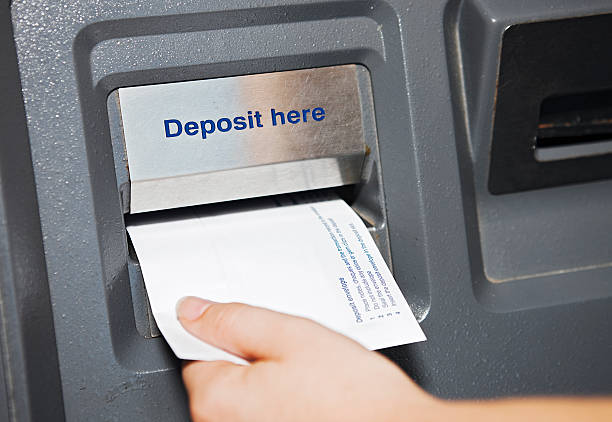 pay day  - hand places deposit envelope in atm slot - deposit slip stock photos and pictures