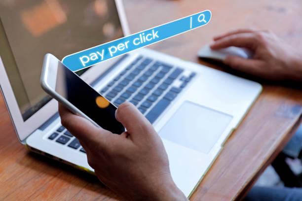 pay-per-klick junger mann hält ein mobiltelefon - computermaus stock-fotos und bilder