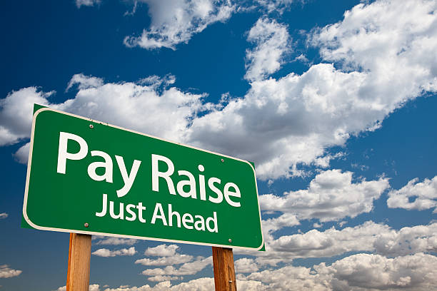 pay raise green road sign - wages stock photos and pictures