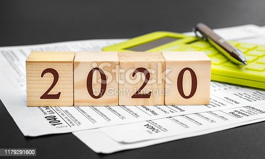 Pay tax in 2020. Wooden cubes with numbers of 2020 year, tax forms and calculator on black.