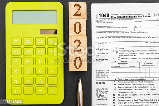 1170746979 istock photo Pay tax in 2020. Wooden cubes with numbers of 2020 year, tax forms and calculator on black. 1183412300