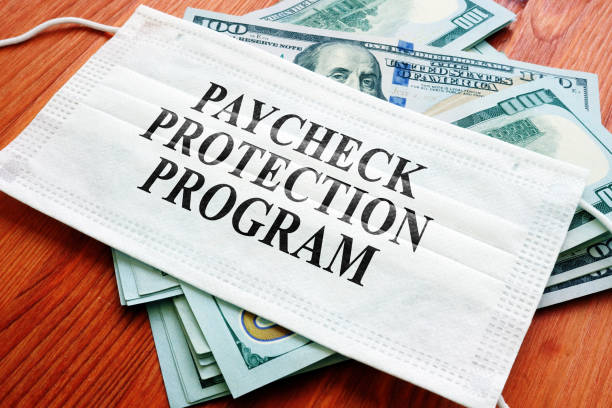 PPP Paycheck Protection Program als SBA-Darlehen auf der Maske und Geld geschrieben. – Foto