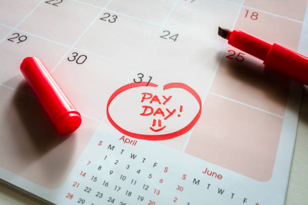 Payday end of month date on calendar with red marker and circled day of salary stock photo