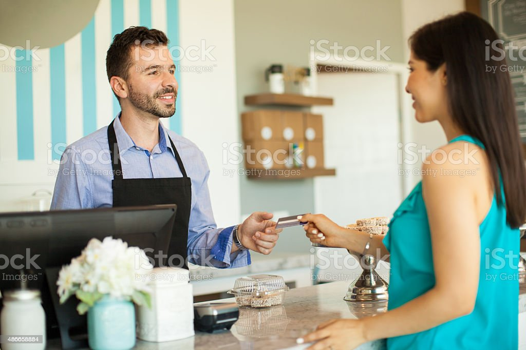 Paying at a cash register stock photo