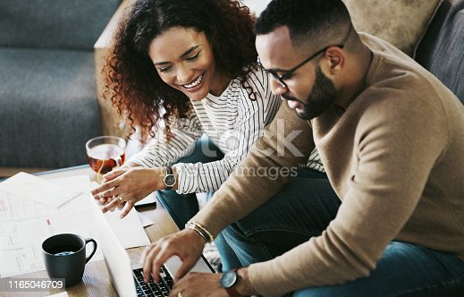 Cropped shot of a young couple using a laptop while going over their finances at home