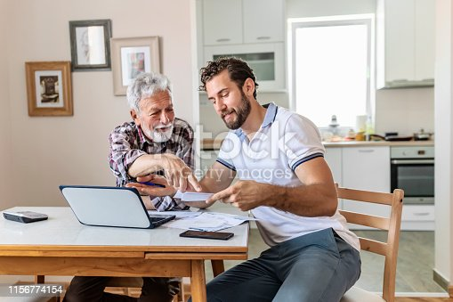 Son Giving Senior Parent Financial Advice at Home. Adult Son Doing Accounts Together With His Senior Father at Home, Planning New Purchase. Family Budget and Finances.