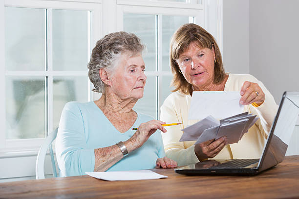 paying bills - social security check stock photos and pictures