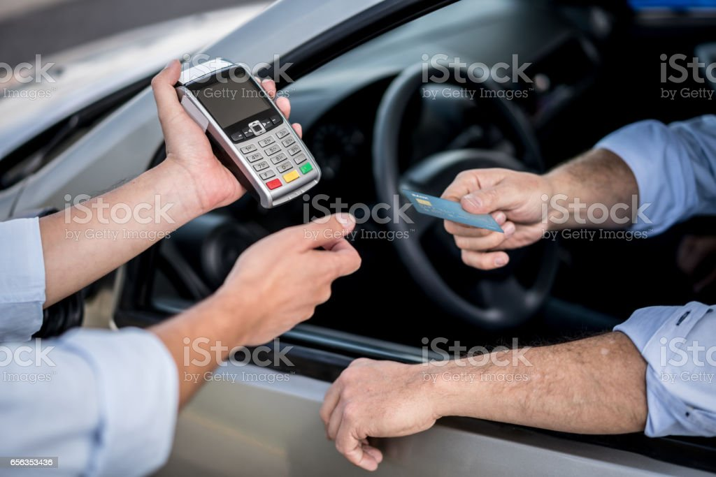 Paying by card at a gas station stock photo