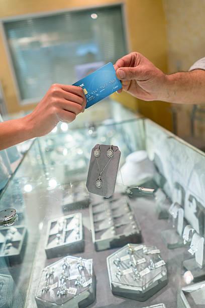 paying by credit card at a jewelry store - diamanten kaufen stock-fotos und bilder