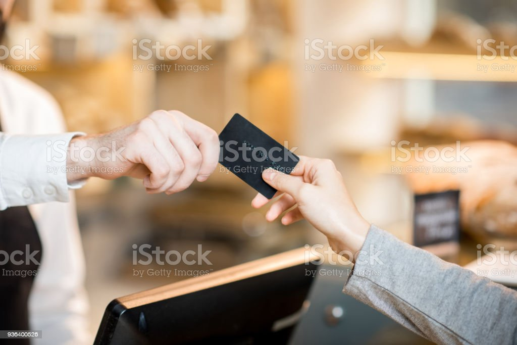 Paying by credit card in the store with bakery products Paying by credit card in the store with bakery products. Close-up view on the hands and card Adult Stock Photo