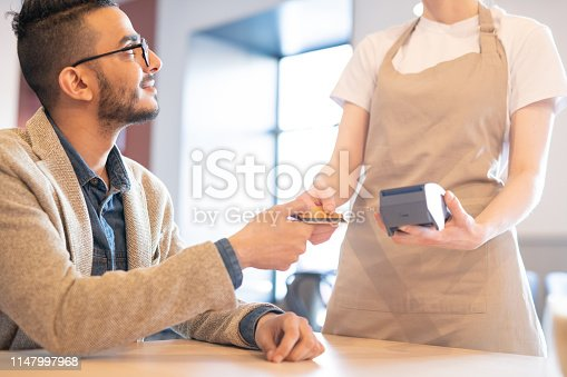 Young elegant businessman giving plastic credit card to waitress in cafe while going to pay for lunch