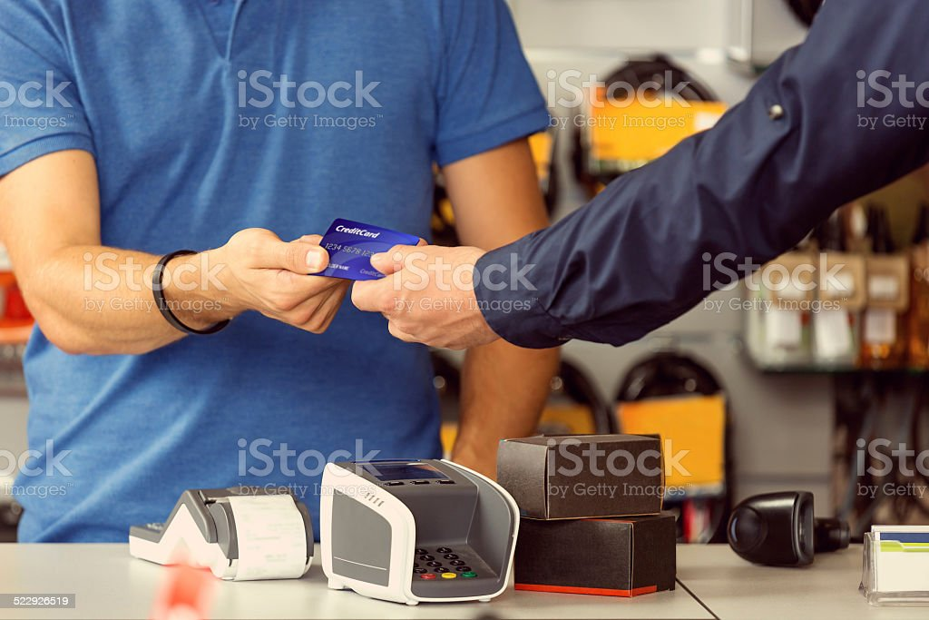 Paying by credit card Customer paying by credit card in a sport store. Focus on hands. Bicycle Shop Stock Photo