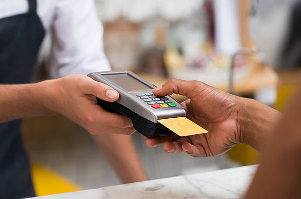 Paying by credit card reader Close up of hand using credit card swiping machine to pay. Hand with creditcard swipe through terminal for payment in cafeteria. Man entering credit card code in swipe machine. smart card stock pictures, royalty-free photos & images