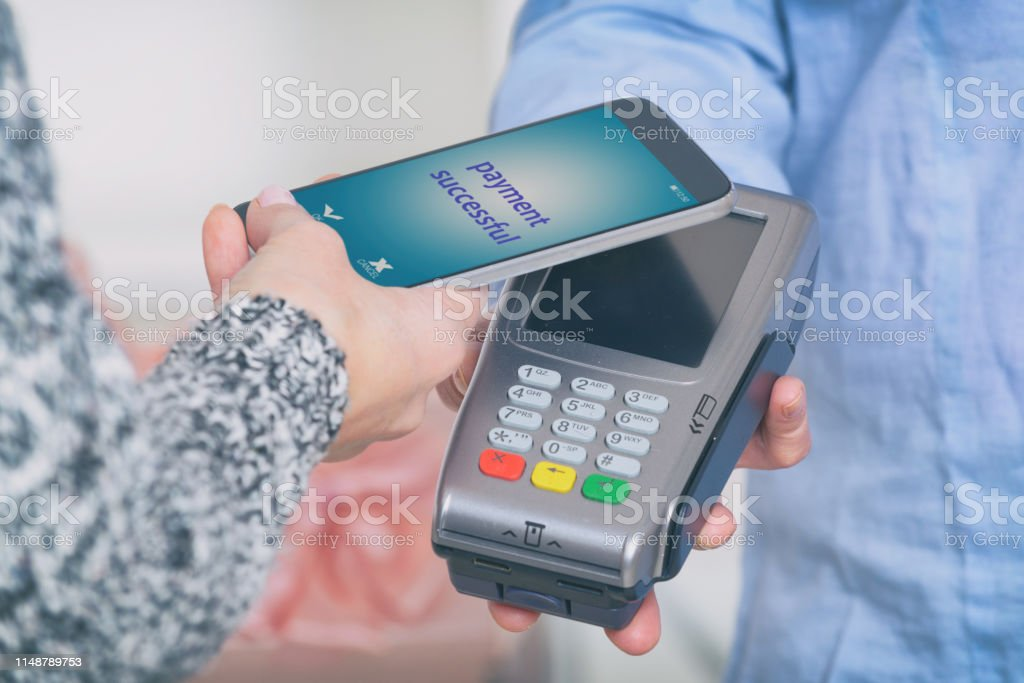 Making contactless payment with smart phone over payment terminal at...