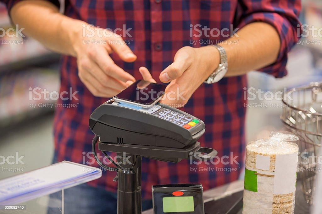 Paying contactless with smartphone stock photo