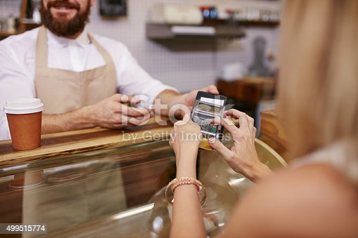 istock Paying for coffee by credit card reader 499515774