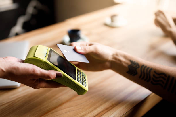 paying the bill with contactless credit card stock photo