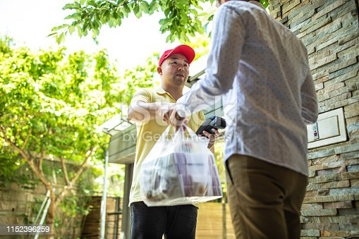 Delivery man with red cap giving to customer take out food in bags in front of house, holding credit card reader for paying