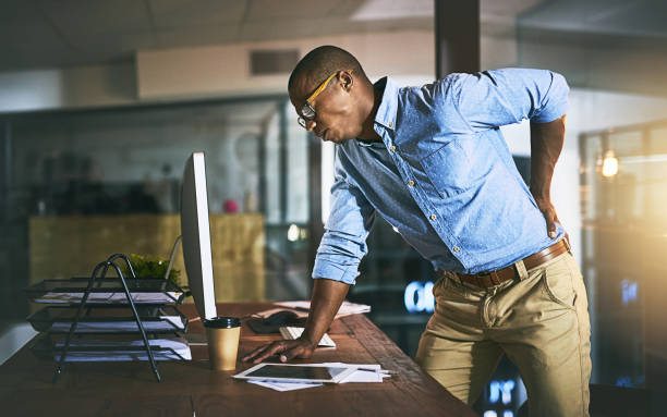 Paying the highest price for success Shot of a young businessman suffering from backache while working at his desk during a late night at work back pain stock pictures, royalty-free photos & images