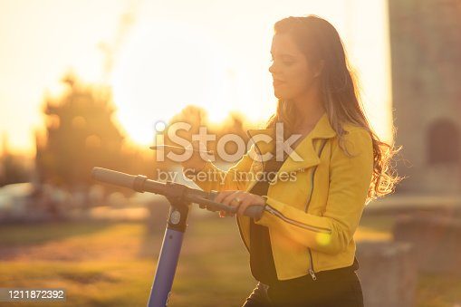 Woman in Auckland city enjoying a ride on electric push scooter.