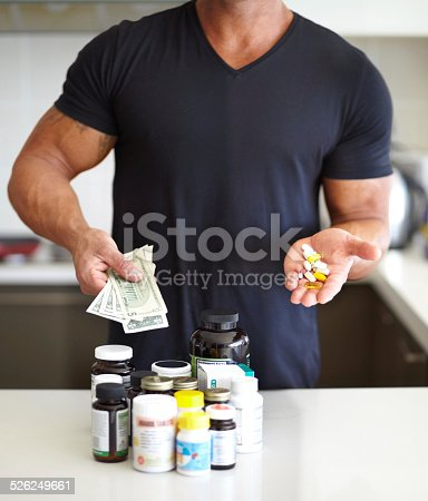 Cropped image of a muscular man holding a handful of pills and holding a pill bottle