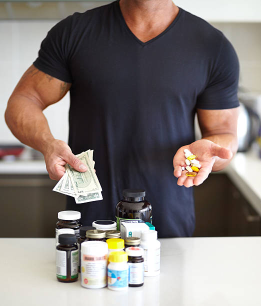 Paying to get into shape Cropped image of a muscular man holding a handful of pills and holding a pill bottle handful stock pictures, royalty-free photos & images