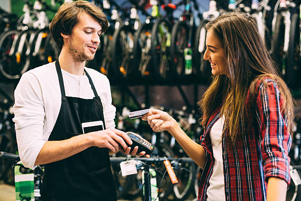 Paying with a credit card Woman paying with a credit card in a bike shop.Woman paying with a credit card in a bike shop. market vendor stock pictures, royalty-free photos & images