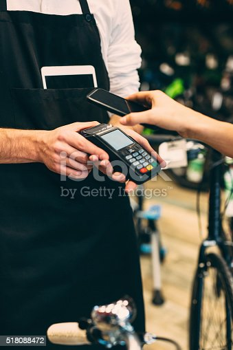 Woman paying with a phone in a bike shop.