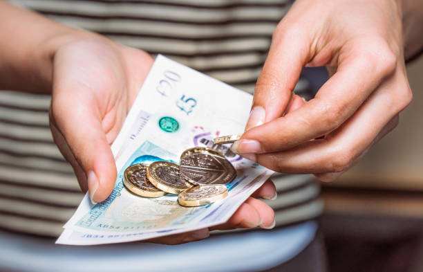 paying with british currency - coin stock photos and pictures