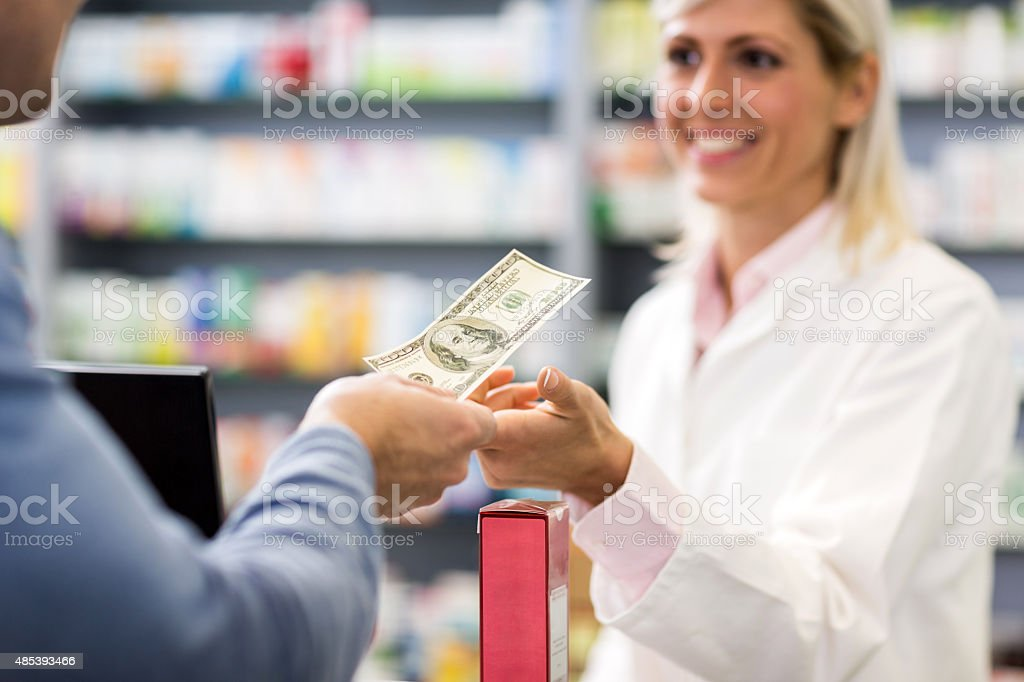 Paying with cash in a pharmacy. stock photo
