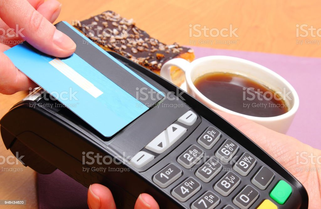 Paying with contactless credit card for cheesecake and coffee in cafe stock photo