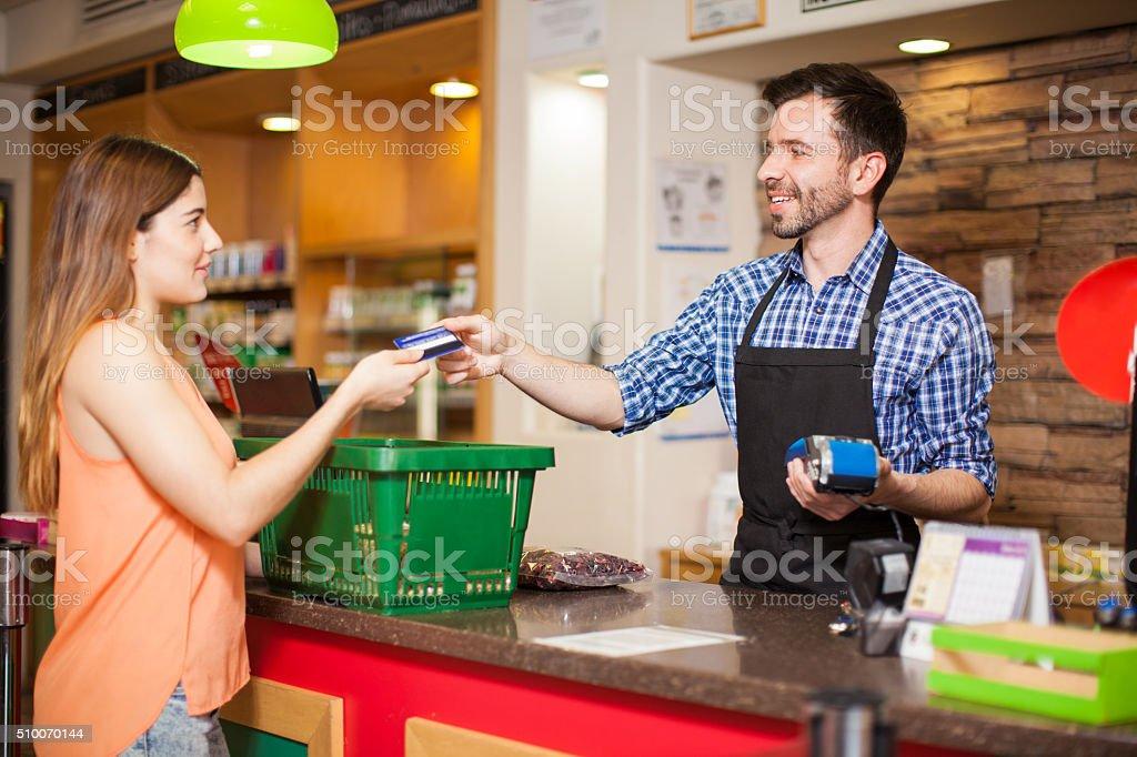 Zahlung mit Kreditkarte in einem Lebensmittelgeschäft - Lizenzfrei Angesicht zu Angesicht Stock-Foto