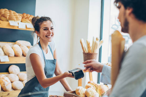 Paying with credit card for a baguette Customer making a credit card payment in a bakery credit card purchase stock pictures, royalty-free photos & images