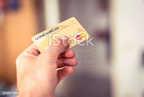 Florence, Italy - June 17, 2013: Man holding and paying with a master card credit card at the mall. Image taken indoors.