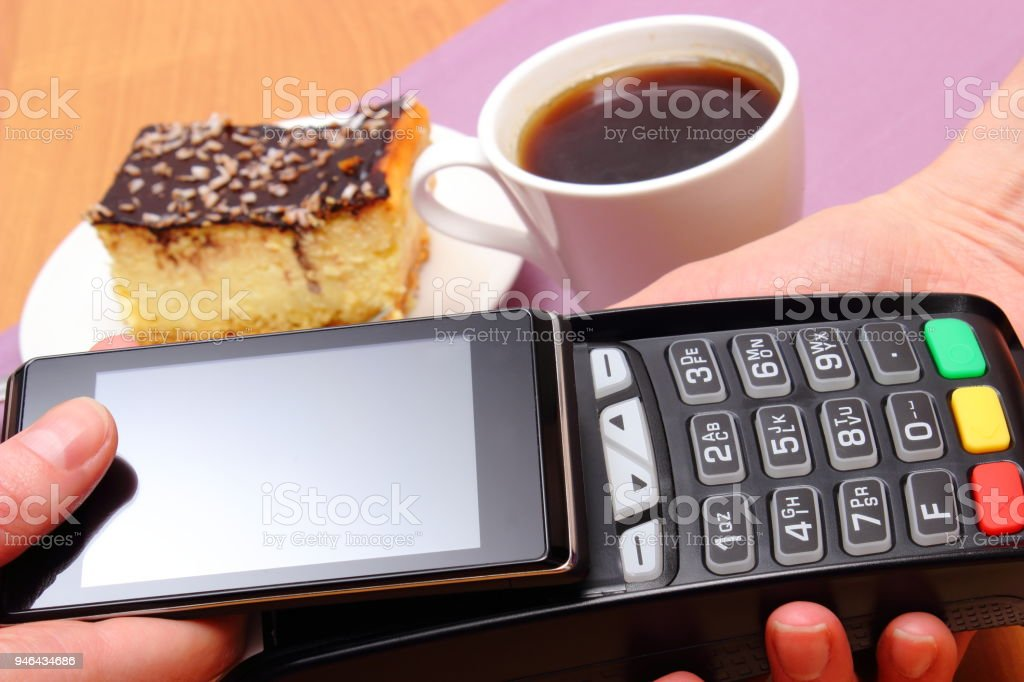 Paying with mobile phone with NFC technology for cheesecake and coffee in cafe stock photo