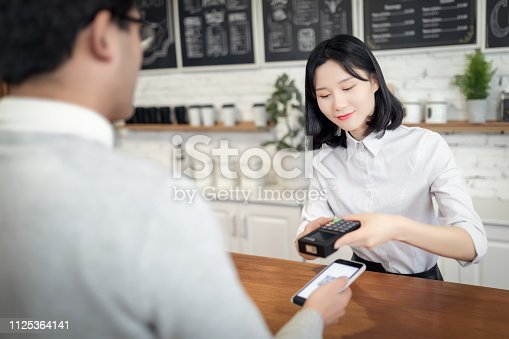 istock Paying with Smartphone in a Cafe 1125364141