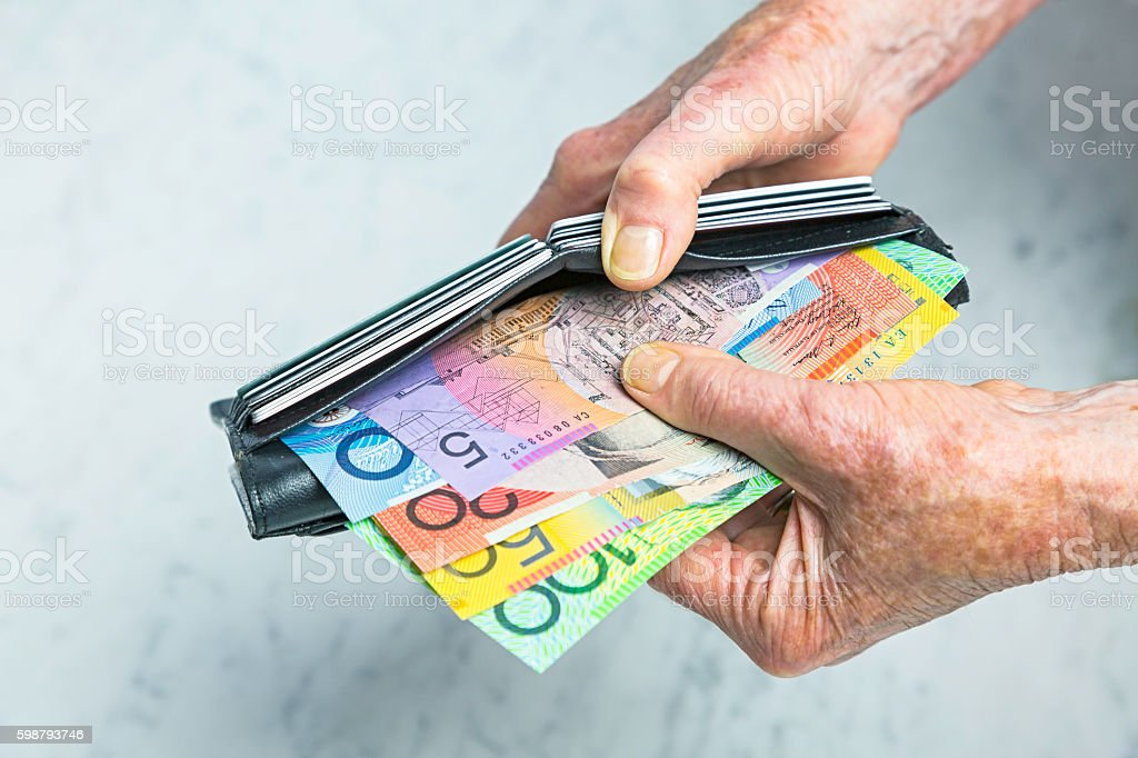 Payment: Close-up senior female hands taking banknotes from purse stock photo
