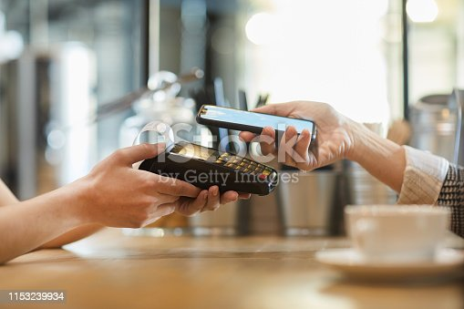 Side view of hands of waitress with electronic device and those of client with smartphone during contactless payment in cafe
