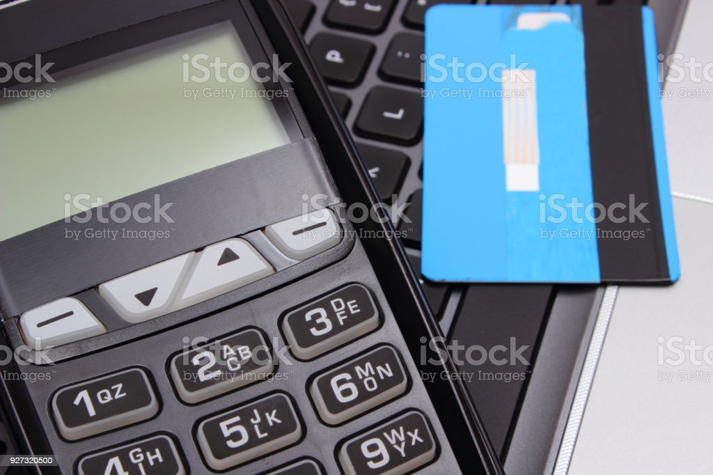Payment terminal and credit card on laptop keyboard stock photo