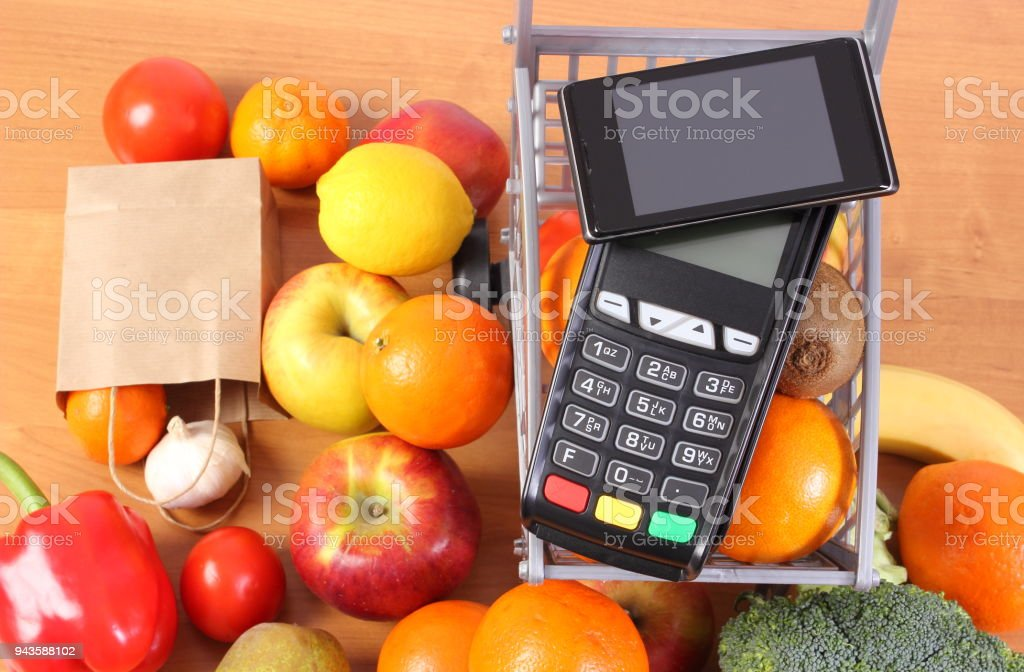 Payment terminal and mobile phone with NFC technology, fruits and vegetables, cashless paying for shopping stock photo