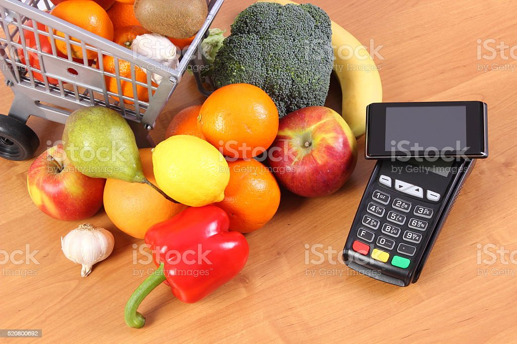 Payment terminal and mobile phone with NFC technology, fruits, vegetables stock photo