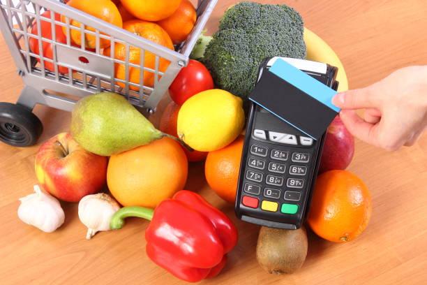 Bezahlterminal mit kontaktloser Kreditkarte und Obst und Gemüse, bargeldlos bezahlen für Shopping-Konzept – Foto