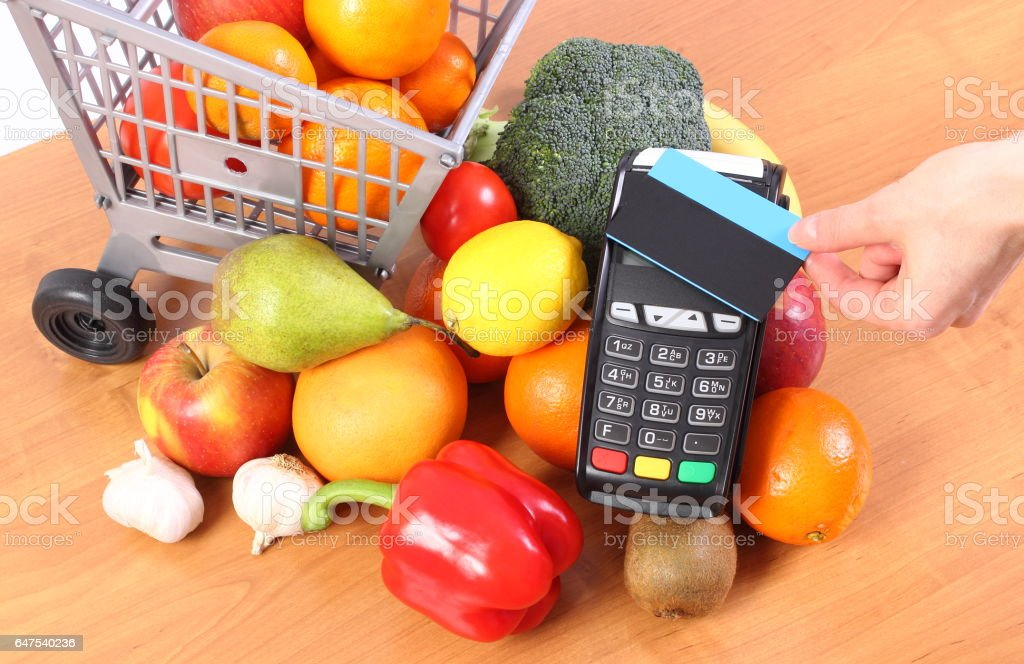Payment terminal with contactless credit card and fruits and vegetables stock photo