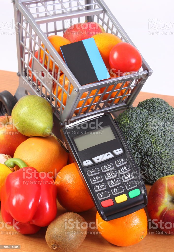 Payment terminal with contactless credit card, fruits and vegetables, cashless paying for shopping stock photo