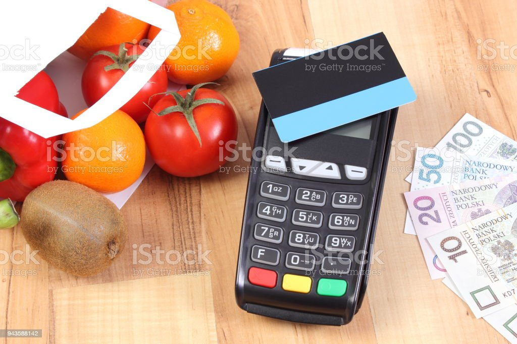 Payment terminal with credit card and polish currency, fruits and vegetables, cashless paying for shopping stock photo