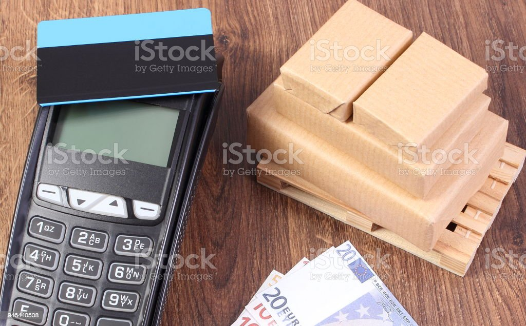 Payment terminal with credit card, currencies euro and wrapped boxes on pallet stock photo